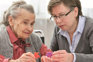 Staff Assisting Memory Care Patient